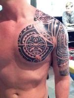Этническая татуировка на груди и плече.